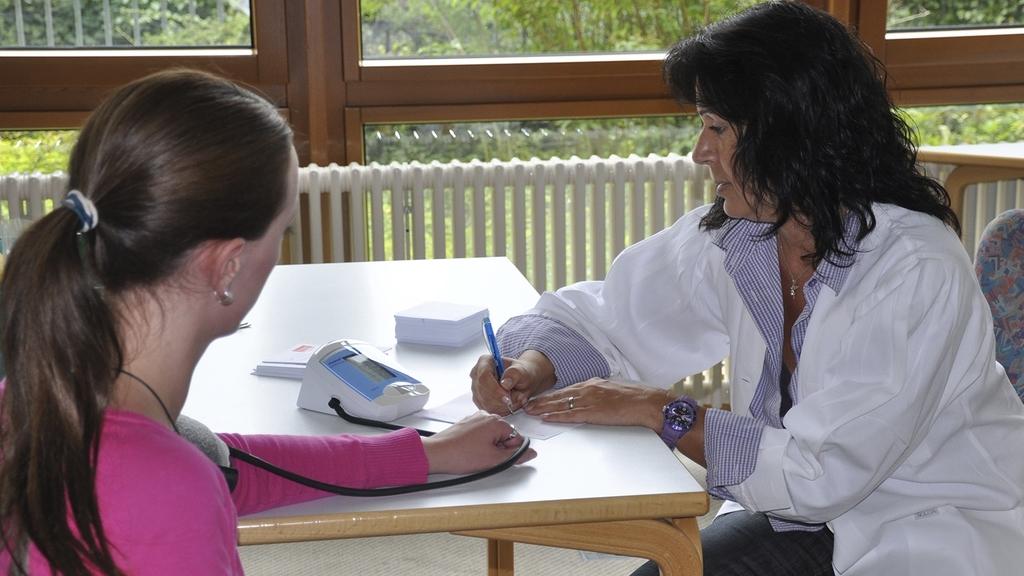 Ärztin mit Patientin beim Blutdruckmessen