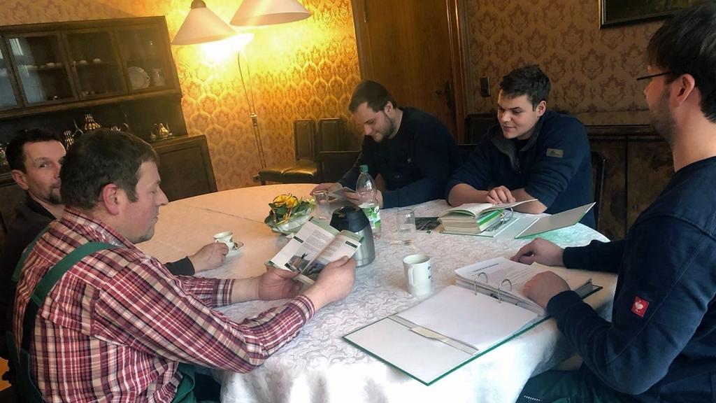 Fünf junge Männer in Arbeitskleidung sitzen in einem einfach eingerichtetem Wohnzimmer an einem runden Tisch und schauen sich Broschüren, Flyer und Ordner an.