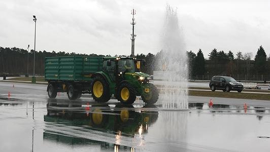 Traktor mit Anhänger fährt auf einer nassen Fahrbahn durch die Wasserfontäne