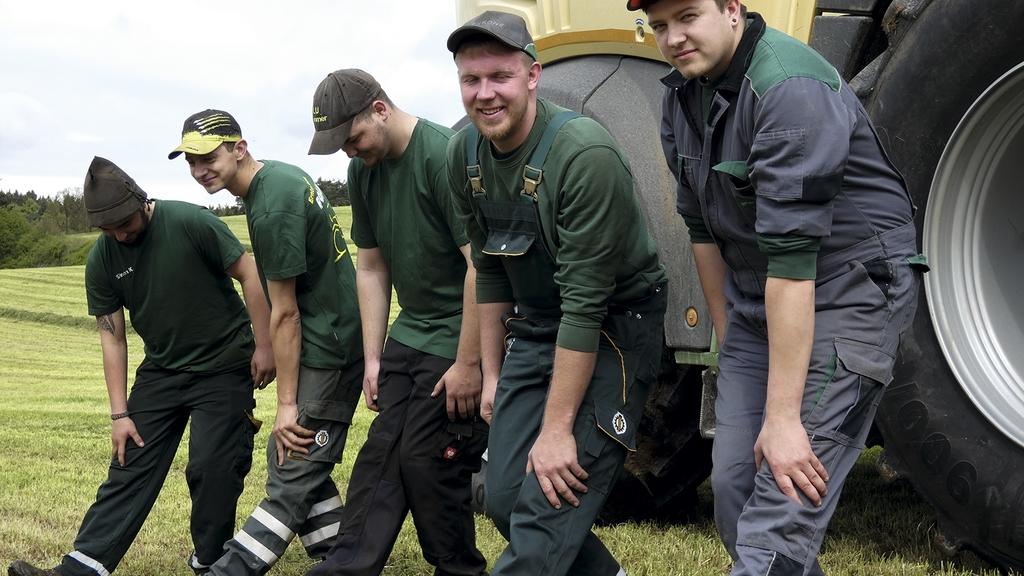 Personen dehnen im Stehen die Wadenmuskulatur. Sie stehen auf dem Feld, im Hintergrund ein Traktor